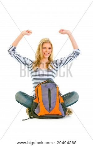 Pleased teengirl sitting on floor with schoolbag and rejoicing her success isolated on white