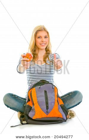 Smiling girl sitting on floor with schoolbag holding apple in hand and showing thumbs up gesture