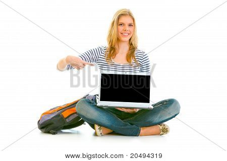 Smiling teengirl sitting on floor with schoolbag and pointing finger on laptop with blank screen