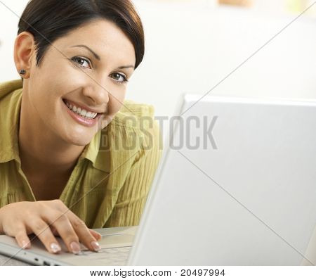 Closeup portrait of happy woman using laptop computer, looking at camera, smiling.
