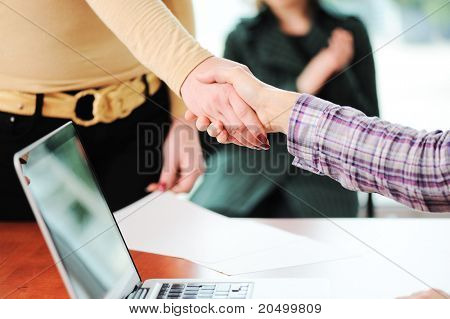 Closing a successful deal with a handshake. Signed contract and applause in the background.