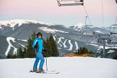 Smiling Skiing Woman Standing In Snow Mountain Under A Ski-lift With Wonderful Winter Mountains Back poster