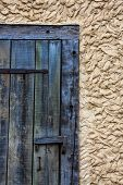 stock photo of hasp  - Corner detail of weathered wood door with hinges and hasp in mud and plaster wall - JPG