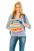 Smiling teen girl with pile of schoolbooks in hands reading isolated on white poster
