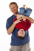 stock photo of tickle  - Adorable toddler boy giggling as Daddy holds him upside down tickling - JPG