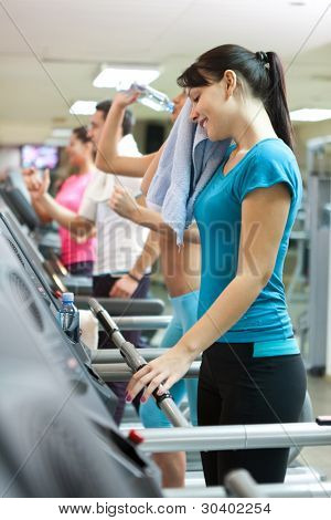 young smiling woman with towel on treadmill, after intensive training