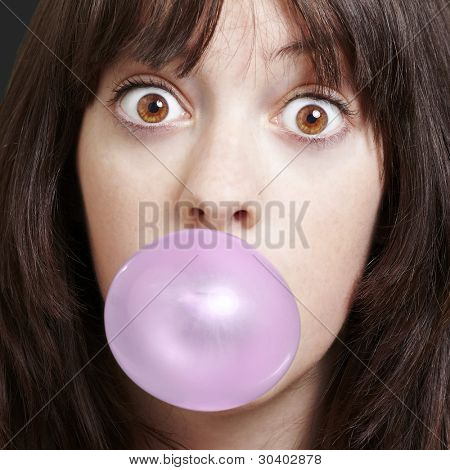 young girl with a pink bubble of chewing gum against a black background