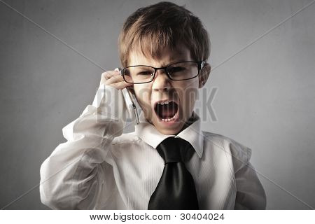Angry child disguised as a businessman screaming on the mobile phone