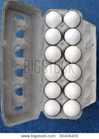 A carton of eggs on blue background