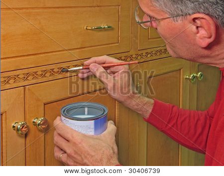Man varnishing decorative trim on an entertainment center