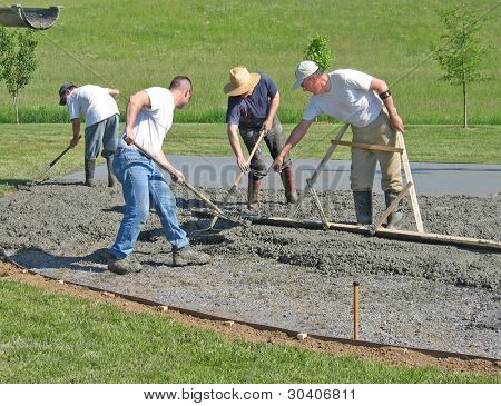 Workers smooth a concrete slab