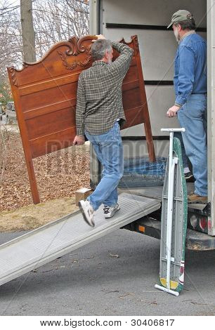 Man carries a headboard onto a moving van