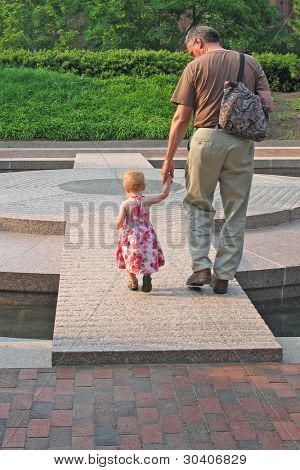 Grandfather walks across plaza with precious granddaughter