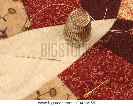 Closeup of quilt with thimble, needle and thread