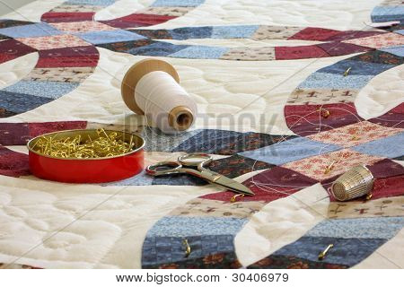 Double wedding ring patterned quilt with quilting tools