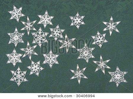 Crocheted snowflakes on holly-patterned fabric background