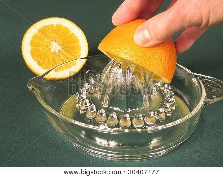 Hand squeezing orange on vintage juicer