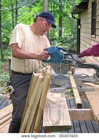 Carpenter cutting balusters for a deck railing with a chop saw