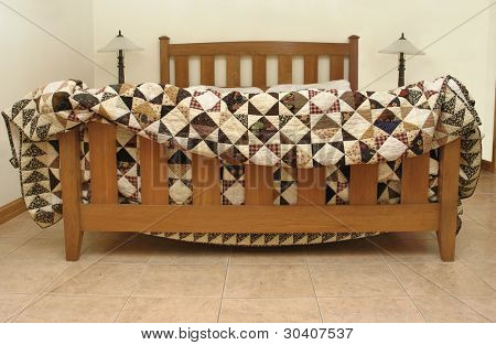 Mission-style bed with geometric handmade quilt