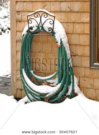 Garden hose in decorative holder, topped by winter snow