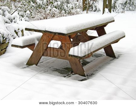 Picnic table covered with snow