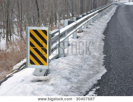 Guard rail and warning sign along rural road