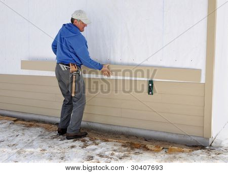 Carpenter using gauge to install fibrous cement siding