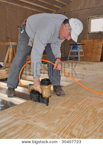 Man nailing plywood sub-floor with nail gun
