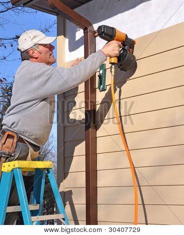 Man installing fibrous cement siding with nail gun