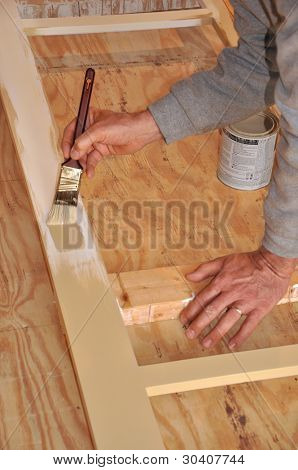 Man's hands shown painting exterior trim assembly