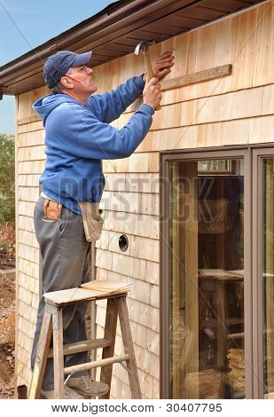 Carpenter nailing cedar shingles to house