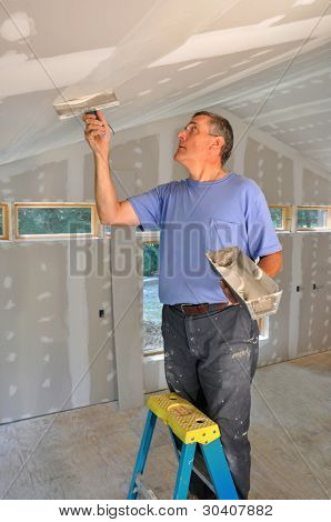 Man applying joint compound to seams between drywall panels on a ceiling