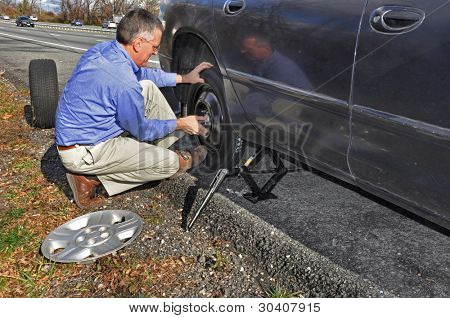 Man changing flat tire along a busy highway