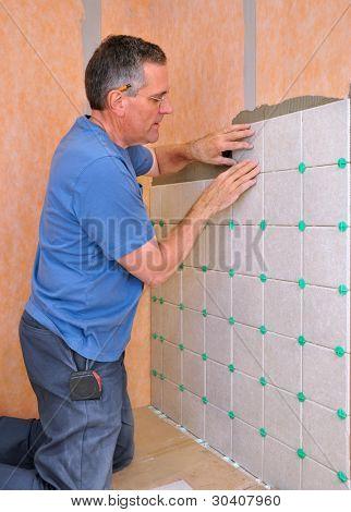 Man installing ceramic tile in shower area of bathroom
