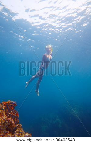 Young woman diving on a breath near corals