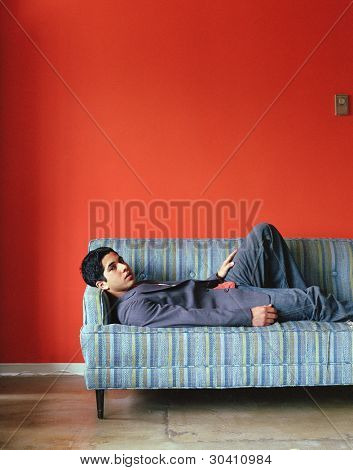 Young man lying down on couch