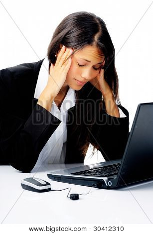 businesswoman working at her desk with laptop computer is stressed, frustrated and overwhelmed by depressing business situations. isolated on white