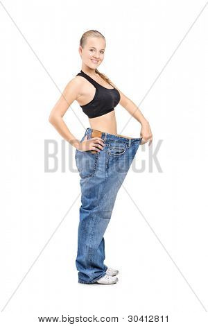 Full length portrait of a happy weight loss female holding her old jeans isolated on white background