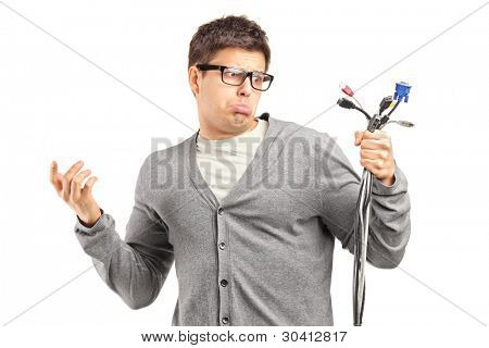 Confused male holding electronic cables isolated on white background