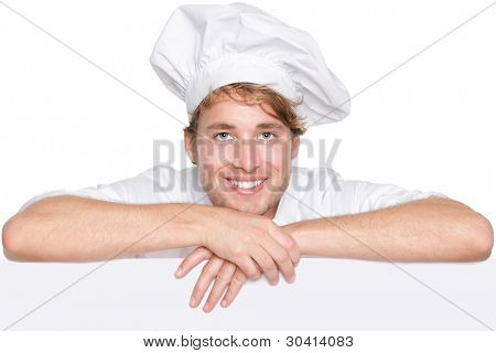 Chef sign. Man chef, cook or baker holding blank white paper billboard sign with copy space for text or menu. Young Caucasian male chef smiling happy isolated on white background.