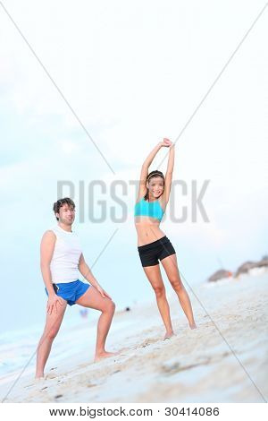Workout couple exercising and stretching on beach. Young interracial couple, Asian woman, Caucasian man working out outdoor.