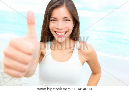 Happy asian woman giving thumbs up success hand sign outside on beach smiling joyful. Sporty fit young mixed race Chinese Asian Caucasian female fitness model outdoors.