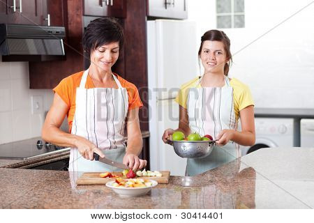 happy mother and daughter making fruit salad in kitchen