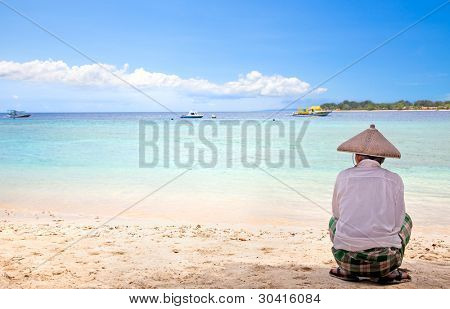Indonesian man with straw hat sitting in shadow on Gilli island beach,  Indonesia