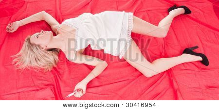 addict woman lies unconscious on the red bed sheet near a syringe