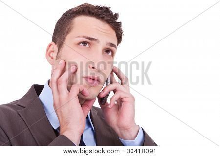 Closeup of a contemplative businessman talking on phone - Copyspace on white