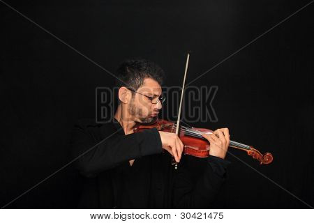 the violinist: Musician playing violin on dark background