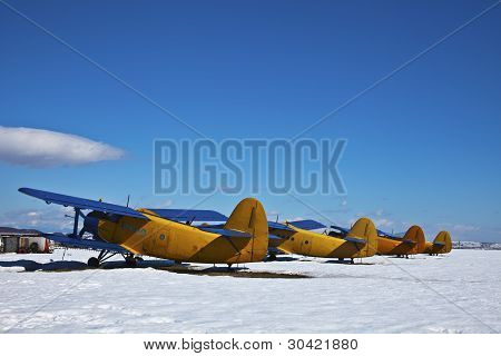 Old Aircraft, Parked In A Field With Snow In A Sunny Day
