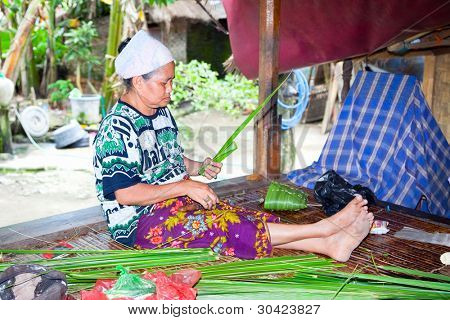 LOMBOK, INDONESIA - FEBRUARY 14 - Sasak woman make basket from leaf of palm  tree on February 14,2012 in Sade village,Lombok.Indonesia. Sasak people are skilled in making baskets for ceremonies