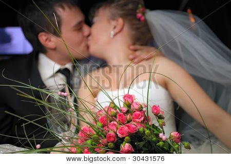 Just married couple kissing in limousine with pink roses bouquet on downstage